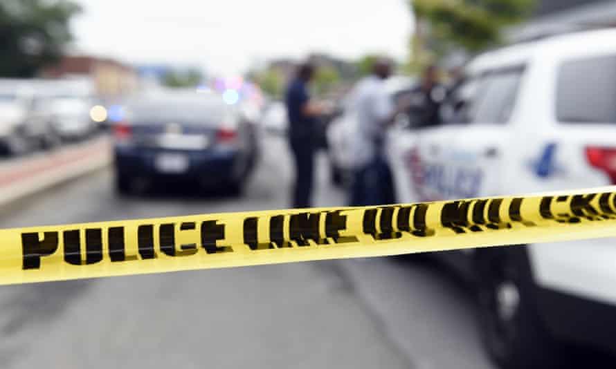 Police officers work behind police tape