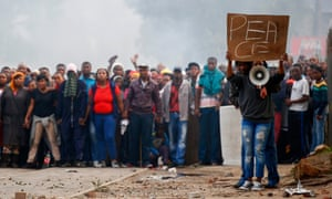 Demonstrators in Masiphumelele, Cape Town, plead for a ceasefire with police