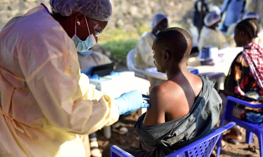 A Congolese health worker administers an ebola vaccine to a man