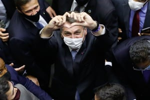 Brasilia, Brazil: President Jair Bolsonaro makes a heart's shape with his hands as he leaves the National Congress after a plenary session of the Chamber of Deputies. The Congress elected two allies of Bolsonaro to head the Senate and the lower house