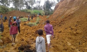 People walking at the site of a landslide near the village of Ekari in Papua New Guinea's highlands.