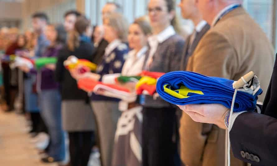 European Medicines Agency staff hold the folded flags of the 28 EU states