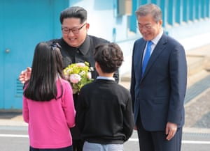 Moon stands by as children present flowers to Kim