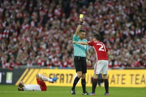 Herrera is shown a yellow card by referee Andre Marriner.