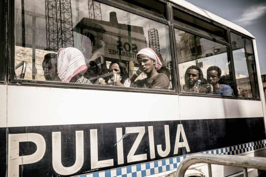 Migrants are taken in a police vehicle