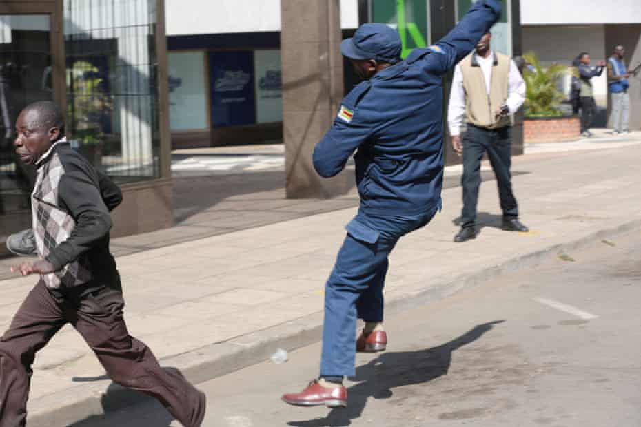 A man runs away from a Zimbabwe Republic Police officer during clashes in Harare.