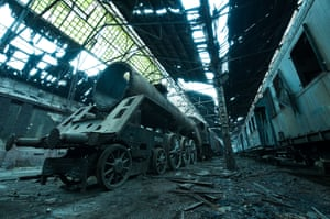 Hungary Abandoned locomotives and carriages in Budapest. The derelict engine shed is located in the middle of a working train depot
