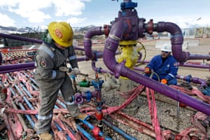 Workers tend to a well head during a fracking operation at an Encana gas well outside Rifle, western Colorado.