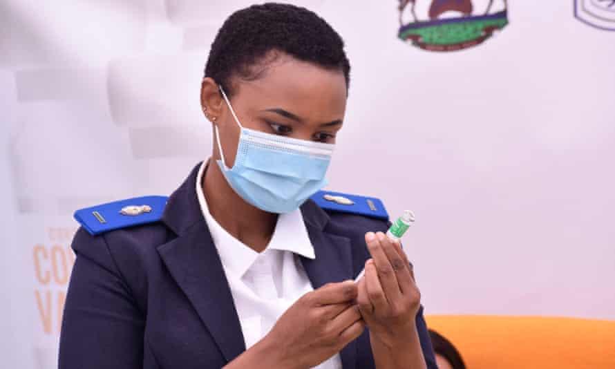 A nurse prepares a syringe with a dose of Oxford/AstraZeneca vaccine