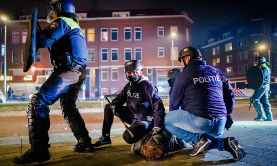 Police officers arrest a man during clashes in Beijerlandselaan.