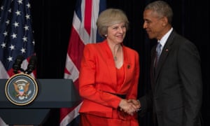 UK Prime Minister Theresa May shakes US President Barack Obama's hand in front of UK and US flags