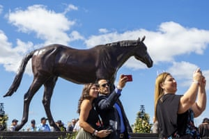 Race-goers take selfies with a statue of Makybe Diva during 2019 Melbourne Cup Day.