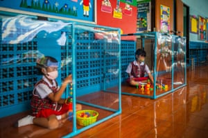 Children play in screened areas used for social distancing at the Wat Khlong Toey school in Bangkok.