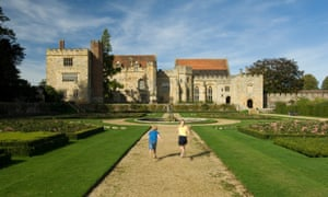 A young boy and girl walking through formal mediaeval gardens towards Penshurst Place in Kent.