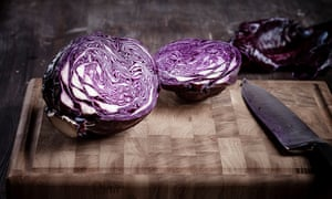 A red cabbage sliced in half on a chopping board.