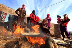 Displaced Iraqis from the Yazidi community, who fled violence between Islamic State (IS) jihadists and Peshmerga fighters in the northern Iraqi town of Sinjar, wait for bread to bake at the Dawodiya camp in the Kurdish city of Dohuk, in Iraq's northern autonomous Kurdistan region, on January 14, 2015. Tens of thousands of members of the Yazidi religious minority were trapped by IS on Mount Sinjar for days in the searing August heat.