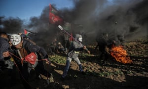 Palestinian protesters throw stones during clashes with the Israeli army on the border.