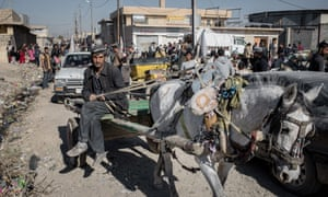 People shopping at a street market in the Gogali neighbourhood of eastern Mosul.