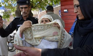 Pakistani police escort Perveen Bibi, who allegedly killed her own daughter by burning her alive after she married the man of her choice, into court in Lahore.