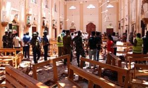 Sri Lankan security personnel walk through debris following the explosion in St Sebastian's Church in Negombo