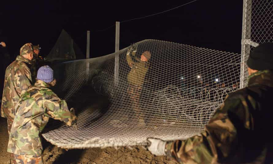 Hungarian soldiers erect a border fence