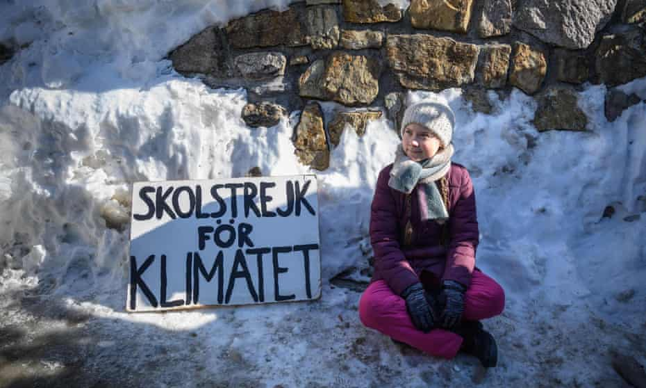 """Greta Thunberg sits next to a placard reading """"school strike for climate"""""""