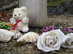 A stuffed bear, shells and flowers are offered at a memorial in Port Arthur.