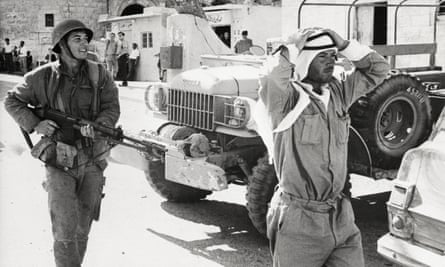 An Israeli soldier marches a captured Jordanian soldier through the streets of Bethlehem.