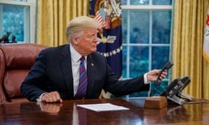 Donald Trump examines a telephone.