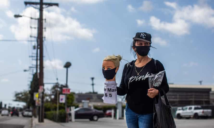 Los Angeles dressmaker Flor Hernandez sells face masks on street after losing her job.