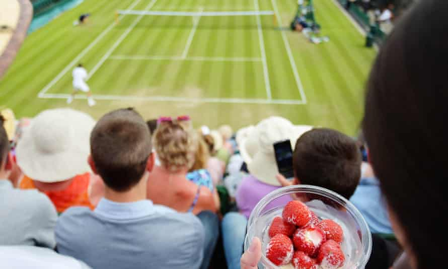 A spectator eats strawberries and cream during a tennis match at the All England Tennis Club in Wimbledon, south-west London