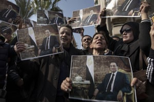 Supporters of ousted President Hosni Mubarak hold posters with his photograph near the cemetery where he will be buried, in the Heliopolis neighbourhood of Cairo, Egypt, 26 February.