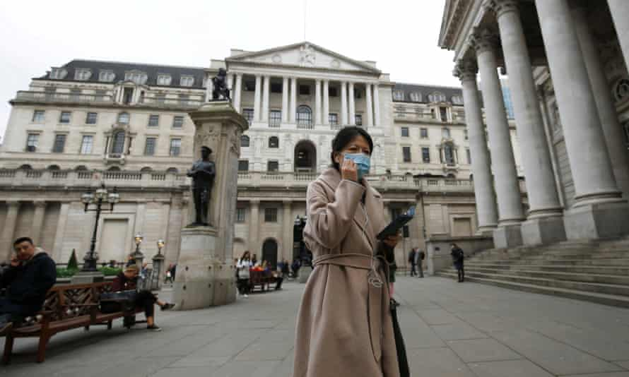 A woman wearing a protective face mask walks in front of the Bank of England.