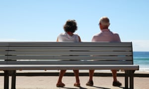 two retirees sit on bench looking out to sea