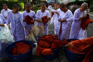 Devotees return their saffron robes after ending their novice monkhood
