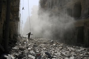 A man walks on the rubble of damaged buildings