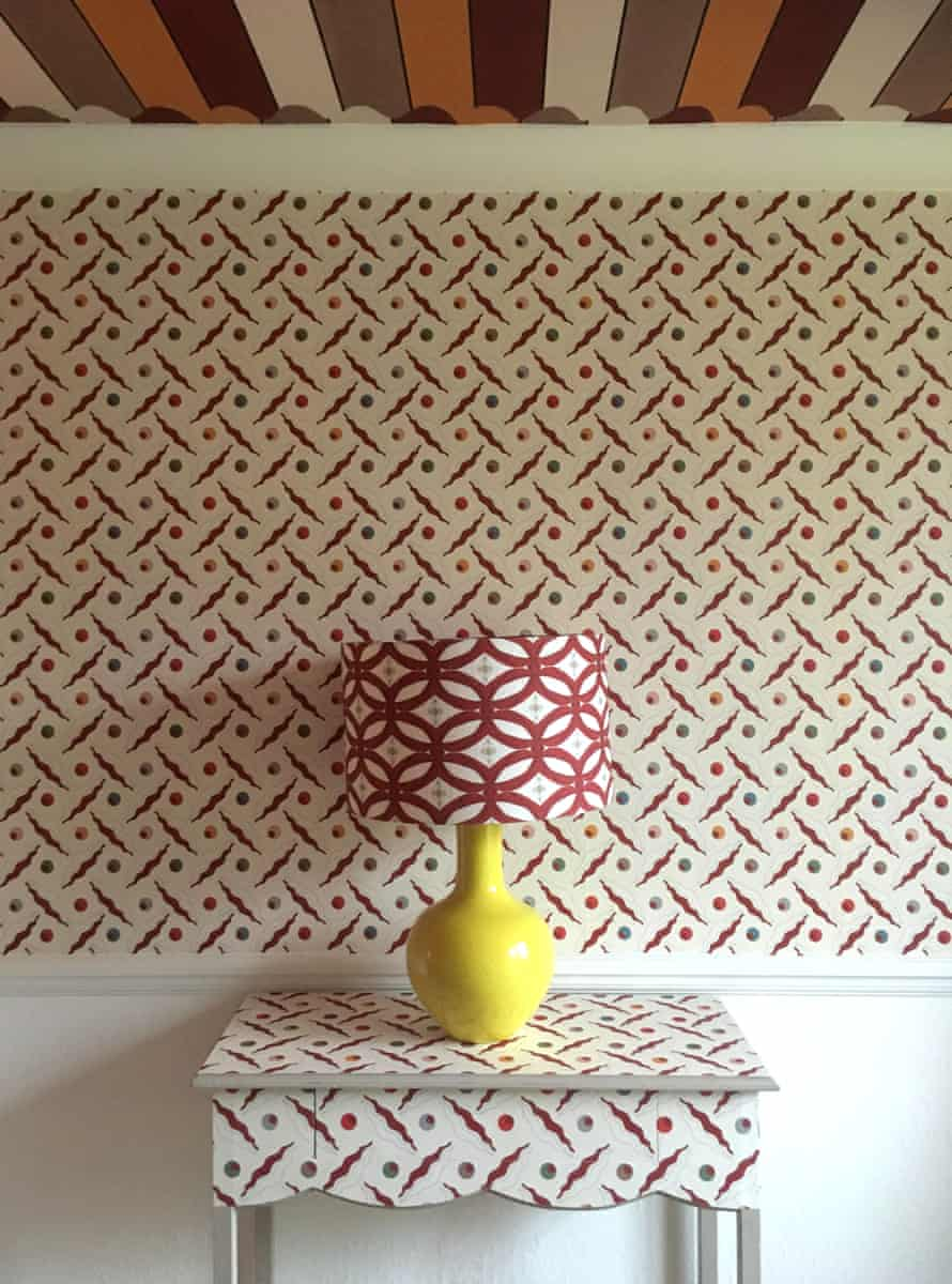 A busy patterned wallpapered wall, the same pattern on a table in front of it, with a lamp on it with a different busy pattern and a stripy ceiling