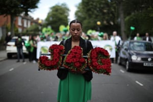 A woman with a floral tribute marks the first anniversary of the Grenfell Tower fire, in which 72 people died
