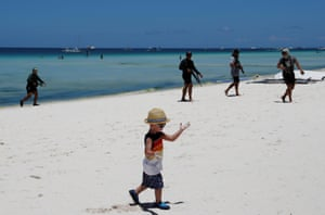 A boy walks along a beach near soldiers taking part in a drill in Boracay, Philippines
