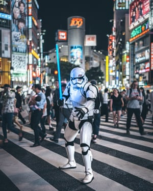 Cosplay, Tokyo. A person dressed in a Star Wars' stormtrooper costumer stands on a busy pedestrian crossing.