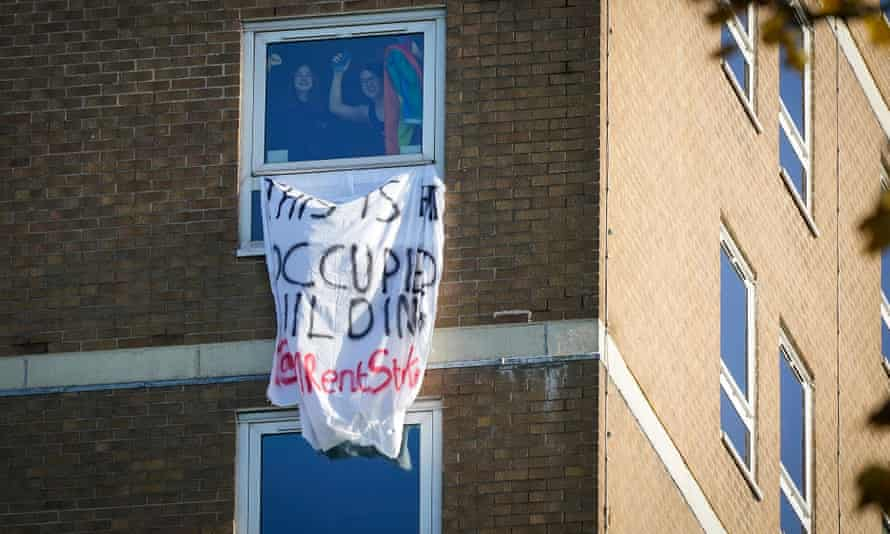 Manchester University students wave from the window of an accommodation tower block that they occupied in protest in November.