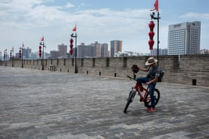 Xi'an, north-west China and a man on a mountain bike prepares for a rideon the 14km-long walls to experience the old and new architecture.