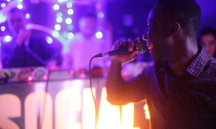 Man holds a microphone while performing on stage at Hip Hop Karaoke.
