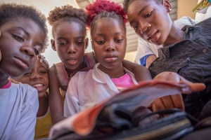 Teenage girls read a book during a break from a session on reproductive health