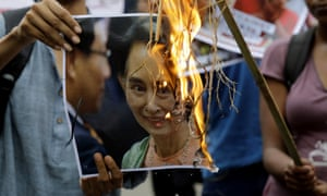 Activists burn a poster featuring a photograph during a protest against the persecution of Rohingya Muslims near Myanmar Consulate in India.