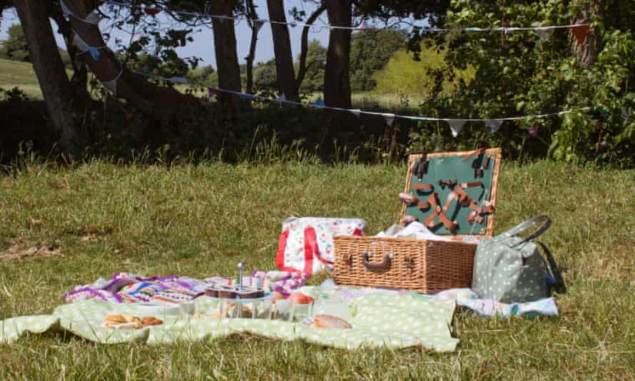 Picnic basket in the countryside with bunting up behind it.