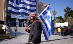 A protester holds a Greek flag in Mytilene, Lesbos.