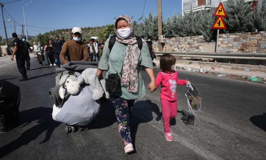 Refugees with their belongings near the burnt remains of Moria refugee camp on Lesbos.