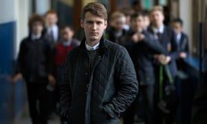 Tim Ramsey in corridor with pupils behind him