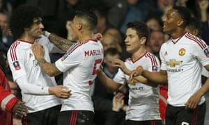 United''s Marouane Fellaini, left, celebrates with team-mates after scoring.